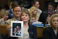 April 27, 2018 - Sacramento, California, U.S. - MELANIE BARBEAU holds a photograph of victims Cheri Domingo and Greg Sanchez during the arraignment of Joseph James DeAngelo, the suspected East Area Rapist.The couple is believed to have been killed by DeAngelo in 1981 in Goleta, Calif. DeAngelo was arraigned in a Sacramento courtroom and charged with murdering Katie and Brian Maggiore in Rancho Cordova in 1978. (Credit Image: © Sacramento Bee via ZUMA Wire)