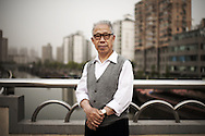 Old chinese man posing in front of the Suzhou River early in the morning, Shanghai, China