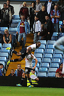 Villa fans leave as Tottenham's Jermain Defoe gets lifted by Lewis Holtby as he celebrates scoring his sides 4th goal. . Capital one cup 3rd round match, Aston Villa v Tottenham Hotspur at Villa Park in Birmingham on Tuesday 24th Sept 2013. pic by Andrew Orchard, Andrew Orchard sports photography.