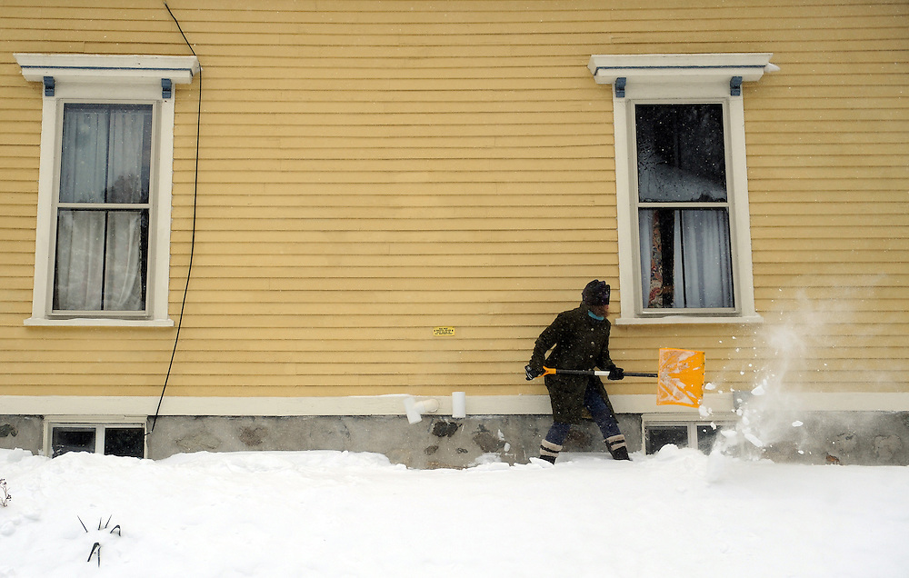Sacha Shawky of Roslindale shovels out during the blizzard, Tuesday, Jan. 27, 2015.