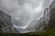 Landscape with view of a valley with majestic mountains with steep cliffs near the Milford Sound, South Island, New Zealand