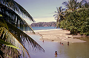 Local children swimming by beach in tidal river at the coast, island of Tobago, 1963