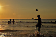 Early morning on a part of China beach in Danang. Silhouettes of a group of teenagers who are playing footbal in the sea. One of them is kicking the ball.