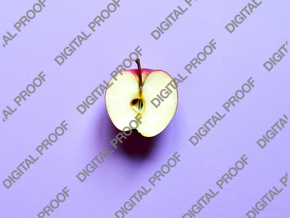 Red apple sliced by half isolated in studio over a violet background