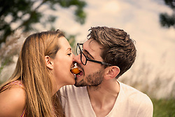 Mid adult couple biting peach together in the countryside, Bavaria, Germany