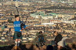 A young piper pipes out the old year on top of Arthur's Seat, Edinburgh with sunshine on Leith behind him<br /> © Jon Davey/ EEm