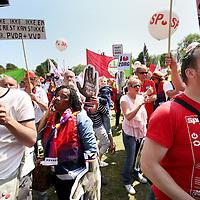 Nederland, Amsterdam , 8 juni 2013.<br /> Landelijke grote manifestatie tegen bezuinigingen in de Zorg.<br /> Vanuit de Czaar Peterstraat arriveerden bussen vol met mensen werkzaam in de zorg om te demonstreren tegen de voorgenomen bezuinigingen in de Zorg. In een protestmars liepen ze gezxamelijk richting het Oosterpark waar de demondtratie plaats vond.<br /> De manifestatie in Amsterdam tegen bezuinigingen in de zorg heeft zaterdag ruim 5000 medewerkers uit de zorg getrokken. Dat meldde een woordvoerster van organisator Abvakabo FNV.<br /> De deelnemers zijn boos over de plannen die de regering heeft met de zorg. Onder het motto 'handen thuis, Rutte!' demonstreren ze tegen de 'afbraakplannen' van het kabinet Rutte.De 5000 zorgmedewerkers komen uit het hele land. Ze verzamelden zich aan de Czaar Peterstraat en liepen vanaf daar naar het Oosterpark, waar de manifestatie werd gehouden. In het Oosterpark ontmoetten de demonstranten in tenten Tweede Kamerleden om over de plannen te praten.'De emoties liepen daarbij soms hoog op', zei de woordvoerster. Ook kwamen enkele sprekers aan het woord, zoals FNV-voorzitter Ton Heerts en SP-leider Emile Roemer. Zanger Gerard Joling verzorgt een optreden. Hij was een van de eersten die zich hardop uitsprak tegen de ideeën van het kabinet, weet Abvakabo FNV.Volgens de bond raken door de plannen van het kabinet 170.000 mensen hun thuiszorg kwijt en verliezen 50.000 thuiszorgmedewerkers hun baan. Nog eens tienduizenden medewerkers in de gehandicaptenzorg en verzorgingshuizen raken zonder werk, concludeert de vakbond.<br /> Foto:Jean-Pierre Jans