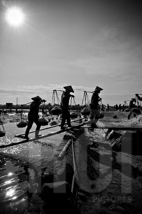 Vietnamese women carry heavy loads of salt in their yokes.  Doc Let, Khanh Hoa area, Vietnam, Asia