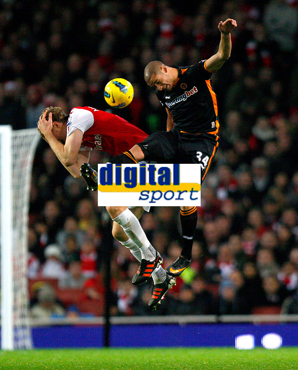 20111227: LONDON, UK - Barclays Premier League 2011/2012: Arsenal vS Wolverhampton Wanderers.<br /> In photo: Per Mertesacker of Arsenal and Adlene Guedioura of Wolverhampton Wanderers leap for the ball.<br /> PHOTO: CITYFILES