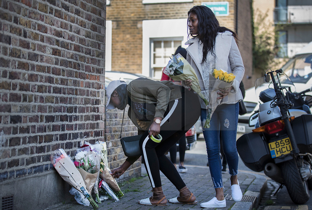 © Licensed to London News Pictures. 05/04/2018. London, UK. Girls lay floral tributes in Link Street near to where 18 year old Israel Ogunsola was stabbed and died from his injuries in Hackney last night . Police were approached by a man suffering from stab injuries at 8pm - he was pronounced dead at 8. 24pm by officers. Photo credit: Peter Macdiarmid/LNP