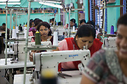 A Nepalese factory worker looks away from her work and listens to her colleagues talking at Surijha Traders garment factory in Kathmandu, Nepal.  The factory room is full of workers sat at sewing machines. The garments produced in the factory are exported around the world. The factory works closely with the Friends of Needy Children organization in providing fair employment opportunities for young Nepalese men and women.