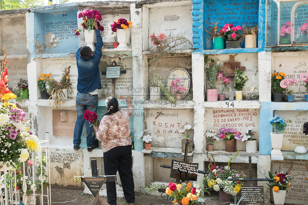 A Mexican family arranges flowers at the grave of a relative in the Nuestra Señora de Guadalupe cemetery during the Day of the Dead festival November 1, 2016 in San Miguel de Allende, Guanajuato, Mexico. The week-long celebration is a time when Mexicans welcome the dead back to earth for a visit and celebrate life.