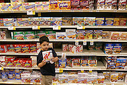 (MODEL RELEASED IMAGE). 5-year-old Brian Fernandez inspects a box of blueberry-flavored Kellogg's Special K Bars while he is on a shopping trip with his mother Diana and her mother, Alejandrina Cepeda, at the local H-E-B supermarket in San Antonio, Texas. (Supporting image from the project Hungry Planet: What the World Eats.)