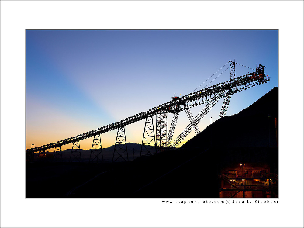 Sunrise behind silhouetted stockpile and conveyor belt in a copper mine at the Atacama Desert, Chile