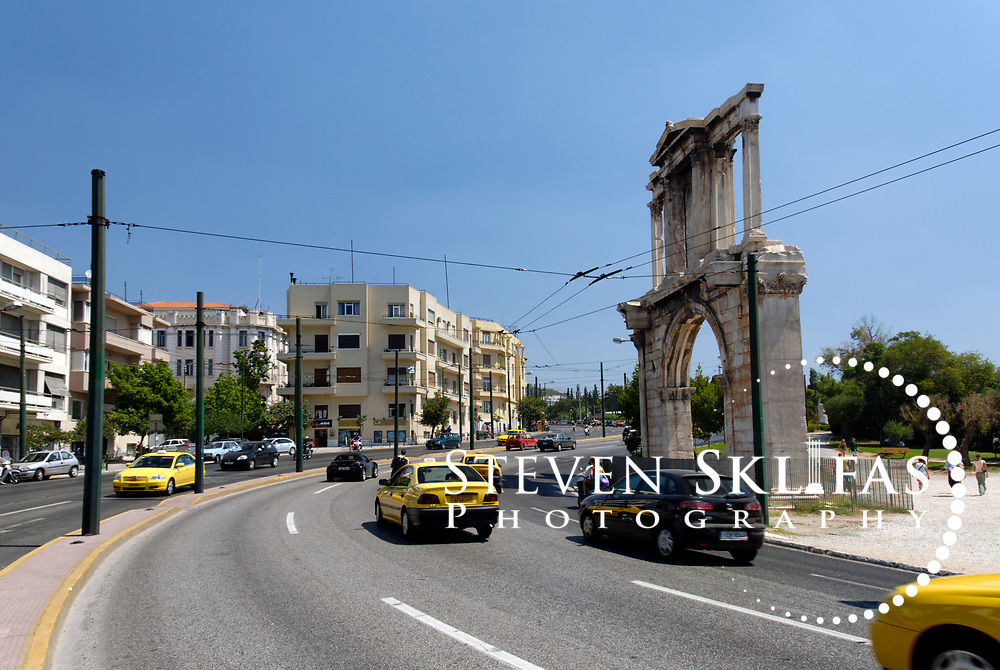 """Hadrian's Arch. Athens. Greece. View of the Arch of Hadrian, a gateway of Pentelic marble built by Roman Emperor Hadrian in 132 AD.  The Arch marked the limit of the old city and the new city of Hadrian. It bears two contrasting inscriptions on each façade. One inscription, facing the Acropolis says """"This is Athens, the ancient city of Theseus"""". The other inscription, says """"This is the city of Hadrian and not of Theseus""""."""