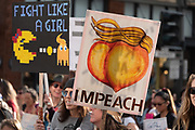 """San Francisco, USA. 19th January, 2019. At the Women's March San Francisco, two women carry humorous signs, one reading, """"Fight like a girl,"""" with a Ms. Pacman chasing a Trump ghost. The other reads, """"Impeach,"""" with an artistic rendering of the fruit with a blond hair combover. Credit: Shelly Rivoli/Alamy Live News"""