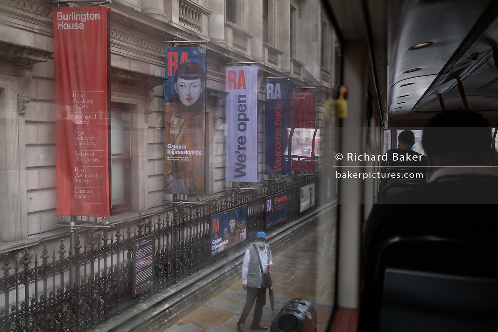 Bus passengers overlook a man wearing a facial covering who stands beneath banners for the Royal Academy's Gauguin summer exhibition, during the Coronavirus pandemic, on 27th August 2020, in London, England.