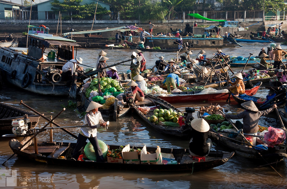 Vietnam's floating markets seem like pure chaos. But watch closely an you'll see a constantly moving order of buying and selling. This market in Can Tho was particularly active during the Tet Lunar New Year period. Robert Dodge, a Washington DC photographer and writer, has been working on his Vietnam 40 Years Later project since 2005. The project has taken him throughout Vietnam, including Hanoi, Ho Chi Minh City (Saigon), Nha Trang, Mue Nie, Phan Thiet, the Mekong, Sapa, Ninh Binh and the Perfume Pagoda. His images capture scenes and people from women in conical hats planting rice along the Red River in the north to men and women working in the floating markets one the Mekong River and its tributaries. Robert's project also captures the traditions of ancient Asia in the rural markets, Buddhist Monasteries and the celebrations around Tet, the Lunar New Year. Also to be found are images of the emerging modern Vietnam, such as young people eating and drinking and embracing the fashions and music of the west.