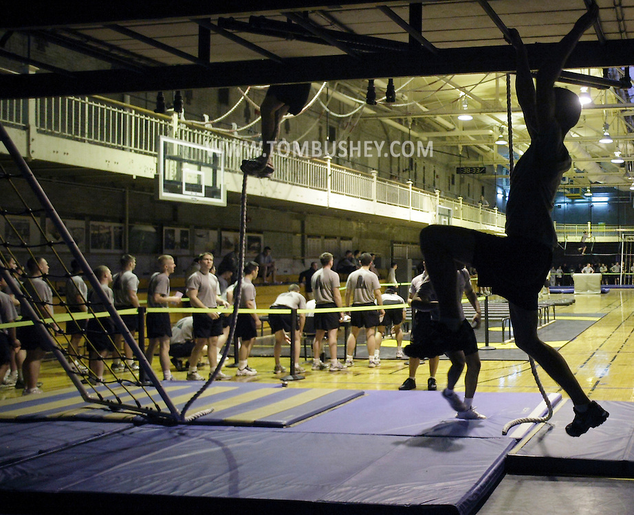 A cadet, at right, moves across the rungs of the horizontal ladder as another cadets climbs a rope and a group of cadets, at left, wait at the starting line for the Indoor Obstacle Course Test in Hayes Gym at the U.S. Military Academy at West Point on Feb. 9, 2010.