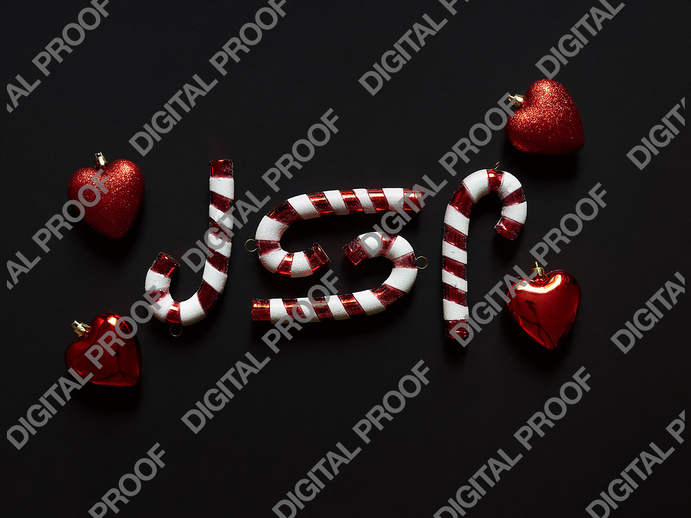 Christmas candy cane  and hearts at studio above view over a black background isolated flatlay