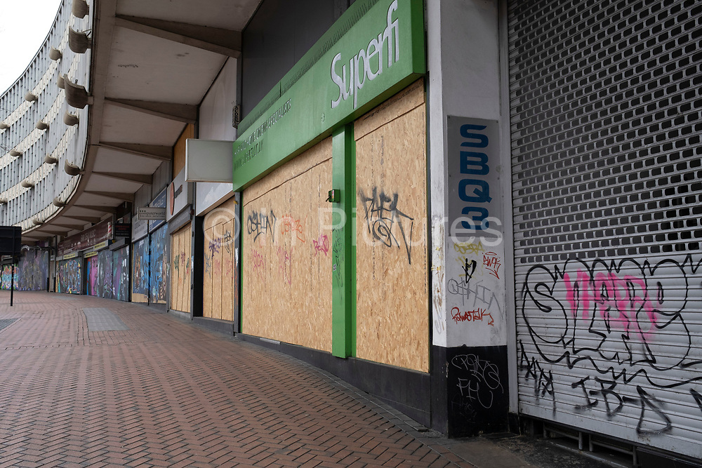 Boarded up shops which are closed in Birmingham city centre due to the Coronavirus outbreak on 31st March 2020 in Birmingham, England, United Kingdom. Following government advice most people are staying at home leaving the streets quiet, empty and eerie. Coronavirus or Covid-19 is a new respiratory illness that has not previously been seen in humans. While much or Europe has been placed into lockdown, the UK government has announced more stringent rules as part of their long term strategy, and in particular social distancing.