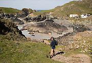 Woman walking at Kynance Cove, Lizard Peninsula, Cornwall, England, UK