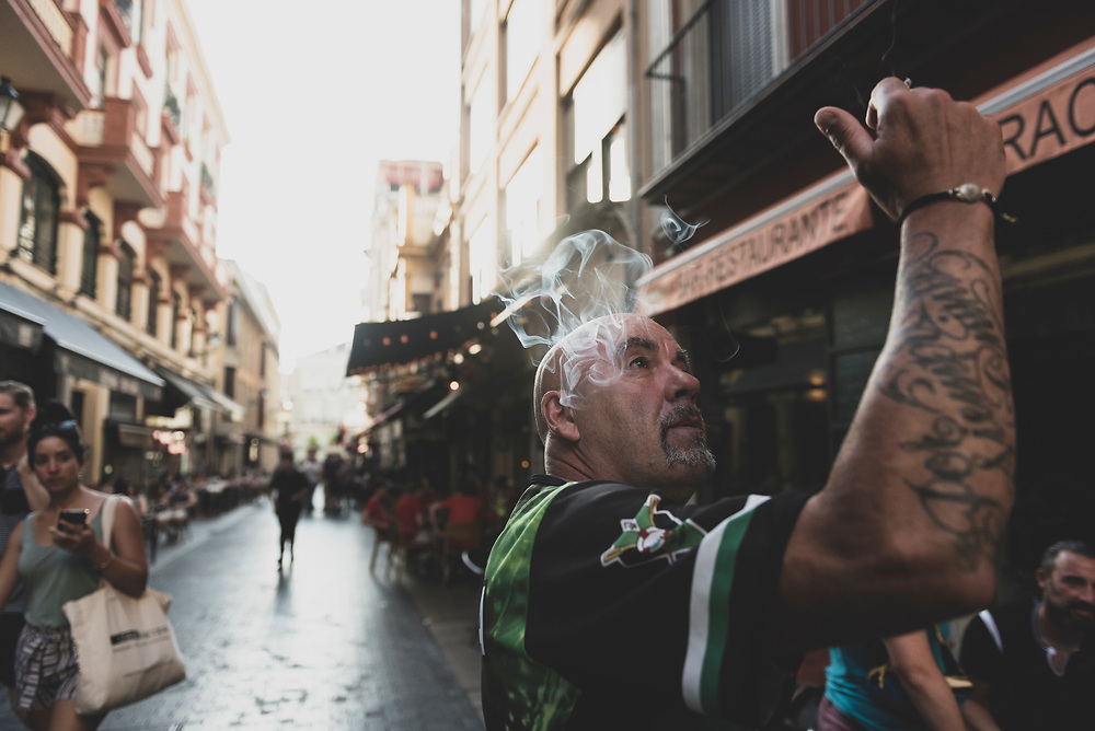 A pilgrim poses as he smokes a cigarette during an evening out and about in the city of Leon, Spain. (June 23, 2018)