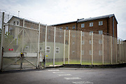 Security fencing around HMP Coldingley. Surrey, United Kingdom. HMP Coldingley is a category C training prison and was built in 1969. Coldingley is focussed on the resettlement of prisoners, and all inmates must work a full working week, within the prison grounds. (Photo by Andy Aitchison)