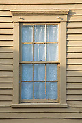 Window of traditional painted wooden clapboard house with lace net curtain in Newport, Rhode Island, USA