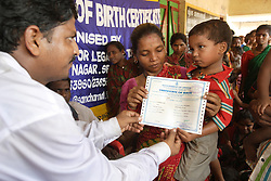 Mahendra Behera, 2, Male, snapped with his mother in red saree.<br /> Parents eagerly gather with their children to receive their birth certificates.<br /> CLAP educates and informs villagers (rural or urban) of the need to register births in order to receive state access to education, healthcare and other social services.  CLAP has worked here for a long time, generating an interest in Birth registration. This slum area is close to the wholesale trader's part of Cuttack city where there is an increasing amount of work for labourers. Programme: Community distribution of Birth Registration. Malgodwan Behera Sahi, Cuttack City, INDIA