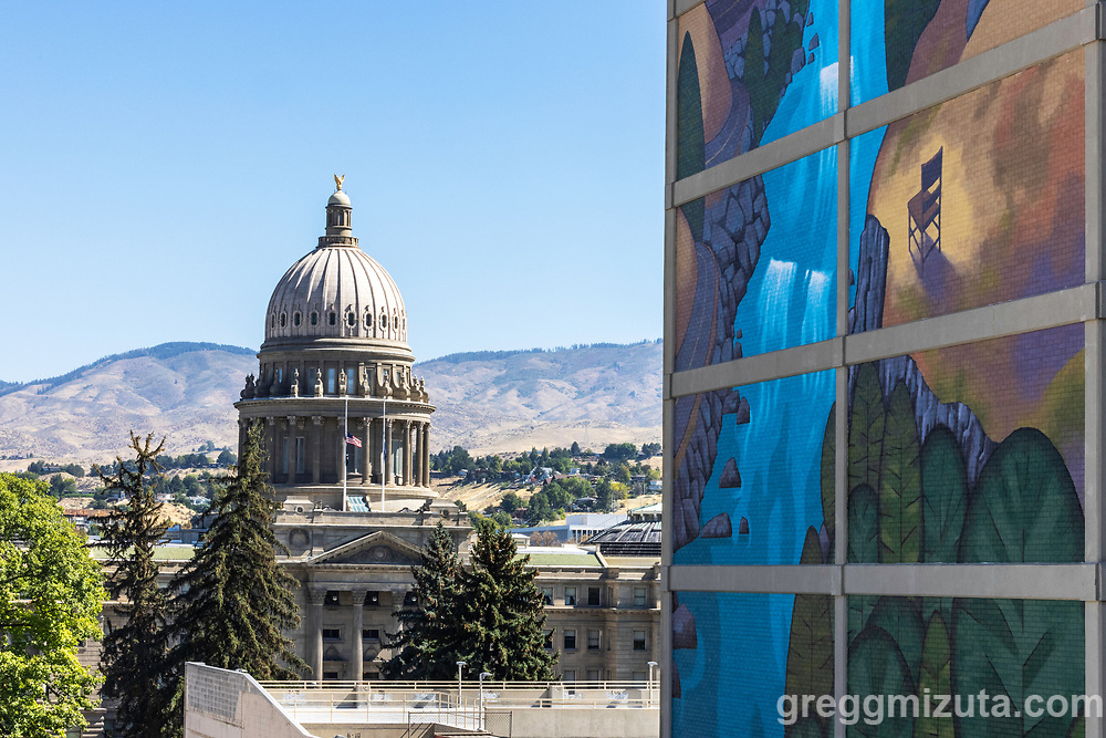 """David Carmack Lewis's mural """"Over the Valley"""" on the Key Financial Center building in downtown Boise, Idaho on August 28. 2021. The mural was completed in June 2020.<br /> <br /> """"Right now the working title is Over The Valley,"""" he told BoiseDev. """"It's sort of a stylized look at the south fork of the Payette.""""<br /> <br /> Lewis said he drove up to the area on his last visit to Idaho when he painted the Fowler mural. """"I love that road. It's kind of funny, this is such a tall building. The viewpoint is looking down at the valley, even though you are looking up at the mural.""""<br /> <br /> He said Key Financial Center's owners put out a call for artists, and he said they selected his because it left the architectural framing at each of the stories intact.""""They saw my other murals. One of the things they liked was I wanted to leave the architectural elements in place. I almost wanted it to be a window. They liked that I took that into account,"""" he said.<br /> <br /> Building co-owner Scott Schoenherr said they looked at more than twenty artists and asked six to submit proposals. He said he liked the creative nature of Lewis' proposal. He pointed to a detail in the rendering as giving the project a little something extra. """"The reason he put the chair there is he wanted people to envision sitting there and looking out over this scene,"""" Scott Schoenherr of building owner Rafanelli-Nahas said. """"I think it's neat. You want to do something that's more than just a landscape but has some creativity."""