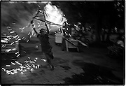 Boy runs with stick bull lit with fireworks.