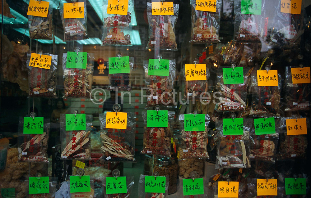 """Displayed in the window of a traditional Chinese medicine shop in Tsim Sha Tsui, Hong Kong, are the labels and plastic bags containing some of the 500 Chinese herbs that are in use today in Eastern herbal remedies, of which 250 or so are very commonly used in the treatment of ailments and diseases. Rather than being prescribed individually, single herbs are combined into formulas designed to adapt to specific needs of individual patients. Herbal formulas contain from 3 to 25 herbs or animal parts, some sourced from endangered species. As with diet therapy, each herb has one or more of the five flavours/functions and one of five """"temperatures"""" (""""Qi"""") (hot, warm, neutral, cool, cold). After the herbalist determines the energetic temperature and functional state of the patient's body, they prescribe a mixture of herbs tailored to balance disharmony."""