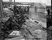 Car Bomb Damage in Dublin (E10)..1972.02.12.1972..12.02.1972..2nd December 1972..On the morning of 2nd December '72 two car bombs exploded in Dublin City. At Sackville Place two busmen were killed as they waited in their car to resume work. The busmen were named as George Bradshaw (30) and Thomas Duffy (23). The bomb was thought to be planted by a Northern Ireland subversive group who hoped to influence legislation going through Dail Eireann in relation to the I.R.A...Image of the car,thought to be the bomb vehicle, tossed against the wall along Eden Quay.