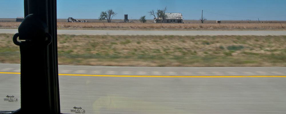 a lone farmhouse in flat rural west Texas along interstate 20  with door post of a classic Mini Cooper automobile in the frame - panorama