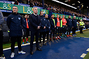 Portsmouth manager Kenny Jackett and his coaching staff and players stand in tribute to John Jenkins ahead of the EFL Sky Bet League 1 match between Portsmouth and Ipswich Town at Fratton Park, Portsmouth, England on 21 December 2019.