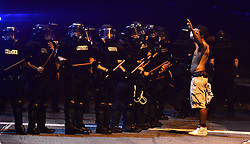 A protestor stands with arms raised, right, near a line of CMPD officers in riot gear on Old Concord Rd. on Tuesday night, Sept. 20, 2016 in Charlotte, N.C. The protest began on Old Concord Road at Bonnie Lane, where a Charlotte-Mecklenburg police officer fatally shot a man in the parking lot of The Village at College Downs apartment complex Tuesday afternoon. The man who died was identified late Tuesday as Keith Scott, 43, and the officer who fired the fatal shot was CMPD Officer Brentley Vinson. Photo by Jeff Siner/Charlotte Observer/TNS/ABACAPRESS.COM