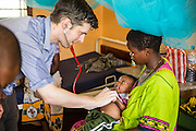 Dr Peter O'Reilly, examines a patient on the children's ward during the daily rounds.  The rounds are attended by all the medical staff who work on that ward, doctors, nurses and attendants. St Walburg's Hospital, Nyangao. Lindi Region, Tanzania.