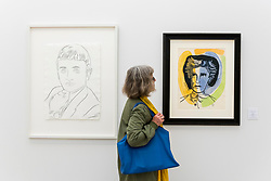 """© Licensed to London News Pictures. 17/05/2019. LONDON, UK. A visitor views """"Jacques Bellini"""", 1983 (L), by Andy Warhol (GBP57,000) and """"Rimbaud"""", 1948 (R), by Fernand Leger (GBP68,000) at the Draw Art Fair London, the first fair in the UK dedicated to modern and contemporary drawing.  58 international galleries have juxtaposed drawings with related paintings, sculptures, photos or videos, in a ratio of approximately 70% to 30%, using drawing as the core concept.  The inaugural show is open to the public 17 to 19 May 2019 at the Saatchi Gallery in Chelsea.  Photo credit: Stephen Chung/LNP"""