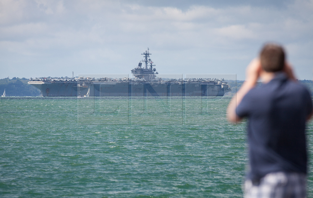 © Licensed to London News Pictures. 01/08/2017. Portsmouth, UK.  A man looks on as the US Navy Nimitz-Class aircraft carrier, USS George H.W. Bush, departs The Solent for a two-week exercise, Exercise Saxon Warrior 17. The ship has been anchored in Stoke's Bay during her six-day visit to Portsmouth, but is now embarking on a multinational exercise taking place around the UK coast involving five nations, including the US and UK. Photo credit: Rob Arnold/LNP