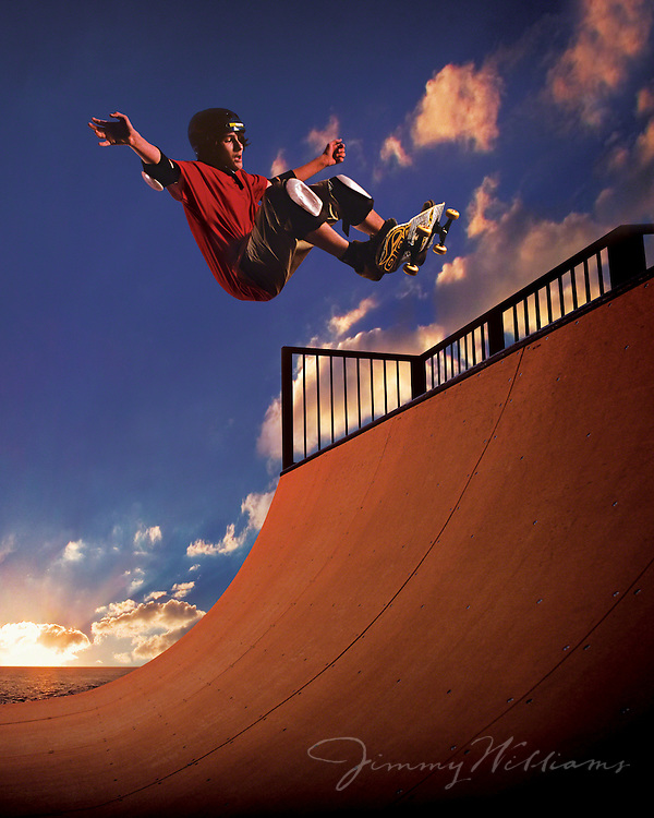 A young boy gets air on his skateboard while skating on a mini ramp at sunset