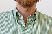 man with short beard wearing a striped shirt