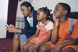 Teenage girl using mobile phone; with her brother and sister sitting on sofa with her,