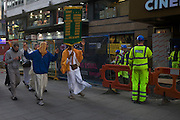 A shift of workmen working in Leicester Sq are amused at some Hare Krishna devotees who dance past singing.