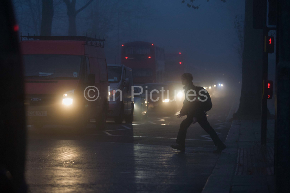 Ignoring a red pedestrian light, a schoolboy dashes out into commuter traffic at dawn on a foggy morning in south London. Despite the dangers of negotiating a busy road, the lad runs off the pavement and into the path of the oncoming cars. It is dawn at around 8.45 on this winter morning, a dark and miserable time of day in this south London suburb from where Londoners start their journeys north into the City. Cars and trucks wait for the lights to change, their headlights shining in the dispersing fog on Denmark Hill.
