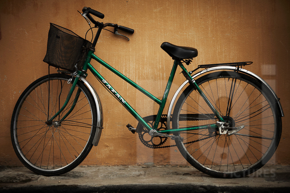 Green Japan bicycle leaning against a wall in Hoi An. Vietnam, Asia