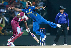 © Licensed to London News Pictures. 29/09/2012. Sri Lankan bowler Lasith Malinga dives in an effort to try stop the ball during the T20 Cricket World super 8's match between Sri Lanka Vs West Indies at the Pallekele International Stadium Cricket Stadium, Pallekele. Photo credit : Asanka Brendon Ratnayake/LNP