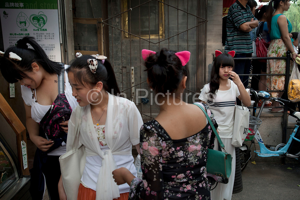 Group of girls wearing cat ears in the Shichahai area, Beijing, China. This is a strange and very common sight in Beijing particularly in this area, to see young women wearing cute fashion ears on their heads. They come in a range of styles and different animals.