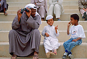 A man and two boys sitting on steps in Kuwait.