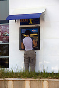 Turkey, Antalya Province, Kas Female tourist at an ATM - Automatic Teller Machine - Model Release Available